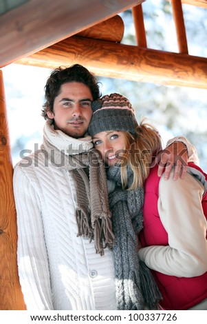 Couple stood hugging on chalet patio - stock photo
