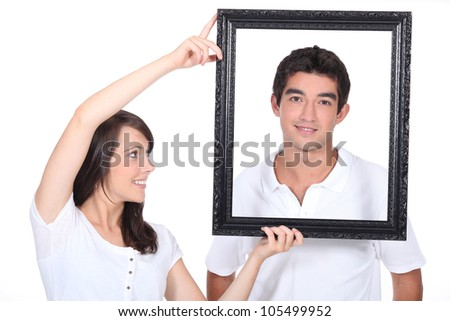 Couple stood with empty picture frame - stock photo