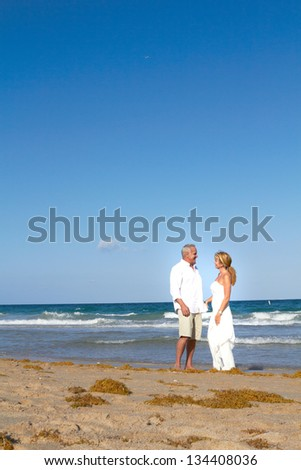 couple strolling around at the beach gazing into the deep blue sea in South Florida.