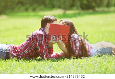 Couple students in love kissing on the grass - stock photo
