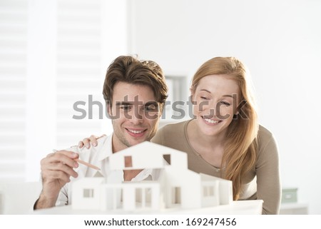 Couple studying a construction project with a model house - stock photo