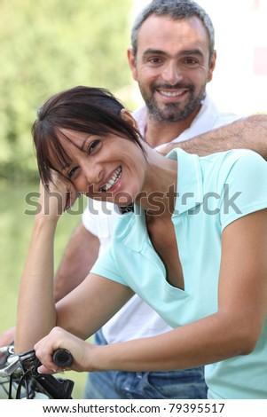 Couple taking a bike ride through the countryside - stock photo