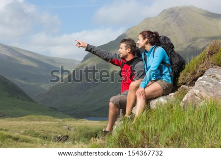 Couple taking a break after hiking uphill with man pointing in the countryside - stock photo