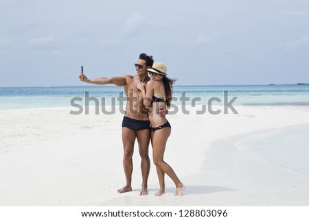 Couple taking a picture of themselves on the beach - stock photo