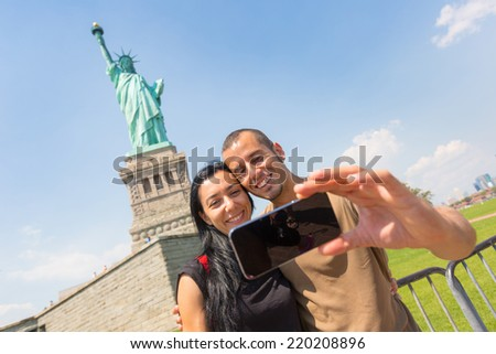 Couple Taking a Selfie with Statue of Liberty on Background - stock photo
