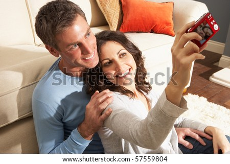 Couple Taking Photograph On Digital Camera At Home - stock photo