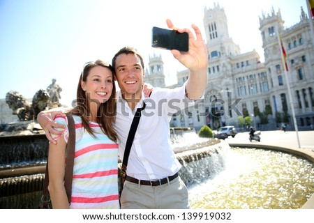 Couple taking pictures in Plaza de Cibeles, Madrid - stock photo