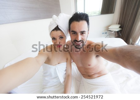 Couple Taking Selfie after Shower. They are in a Modern Hotel Room, They wear white towels and the Woman also has a towel around her Head. They hold the Smart Phone together and Look at it. - stock photo