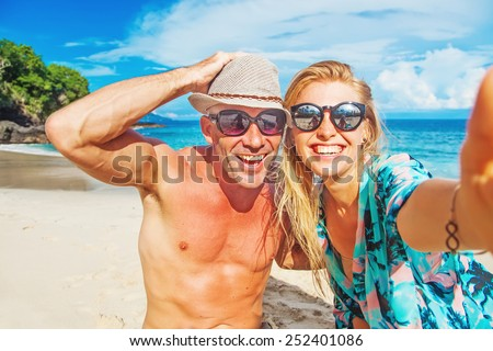 couple taking selfie on a beach - stock photo