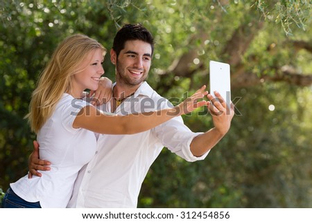 couple taking selfie with digital tablet, selective focus - stock photo