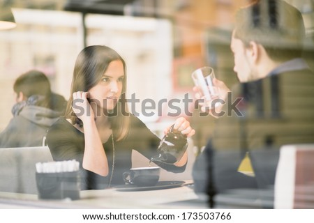 Couple talking and drinking tea in coffee shop - stock photo