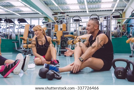 Couple talking with friends sitting on the floor of a fitness center after hard training day - stock photo