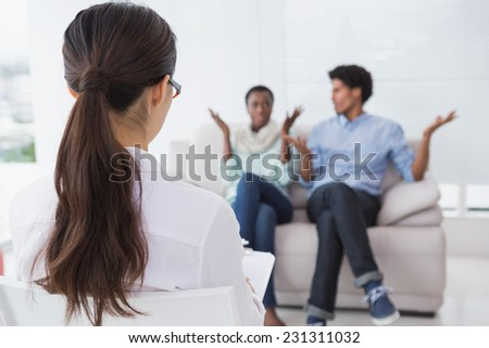 Couple talking with their therapist in therapists office - stock photo