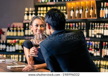Couple tasting red wine in a wine shop