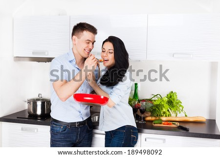 couple tasting the meal in their kitchen happy smile, man feed woman with spoon, cooking at home - stock photo