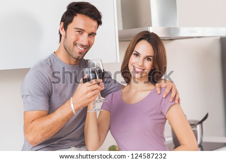 Couple toasting and looking at camera in kitchen - stock photo