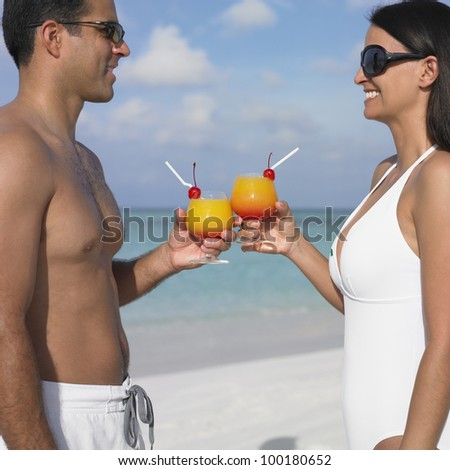 Couple toasting each other at the beach - stock photo