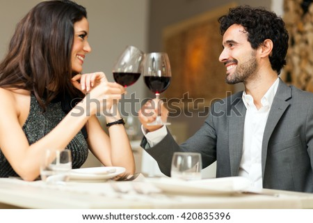 Couple toasting wineglasses in a luxury restaurant. Focus on the woman
