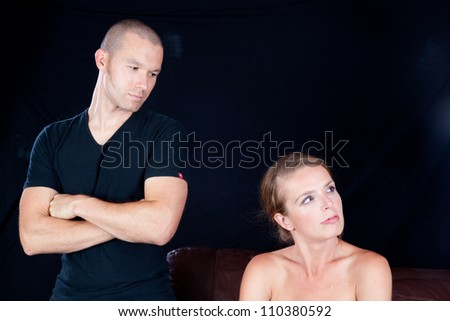 Couple together and angry at each other, he has his arms crossed and glares at her while she looks away - stock photo
