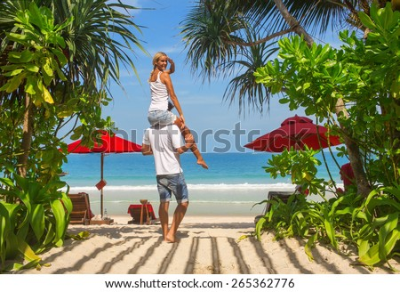 Couple  together during summer holidays vacation on Thailand tropical sand beach.Girl looks in camera,looking fresh and happy.Sea and clear sky on background. - stock photo