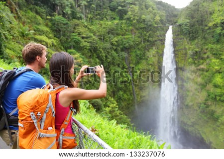 Couple tourists on Hawaii by waterfall. Tourist taking photo pictures of Akaka Falls waterfall on Hawaii, Big Island, USA. Travel tourism concept with multicultural tourist couple. - stock photo