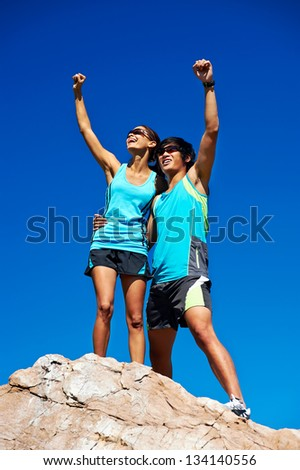couple trail running on mountain at top celebrating with confident smile and healthy lifestyle - stock photo
