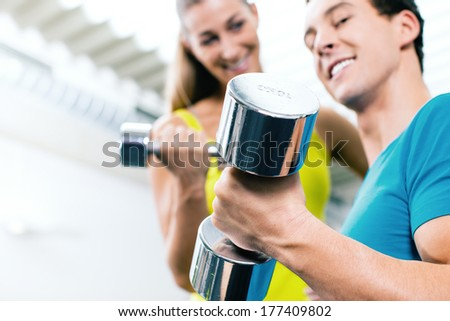 Couple training for fitness in gym with weights