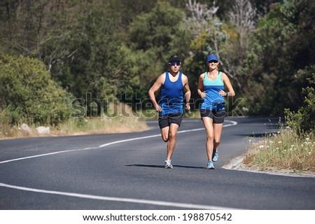 Couple training together for marathon on road run - stock photo