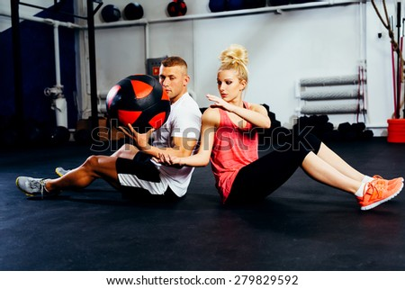 Couple training with exercise ball at gym - stock photo