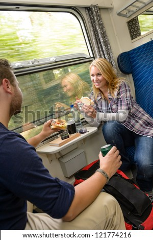 Couple traveling by train eating sandwiches hungry smiling woman man - stock photo