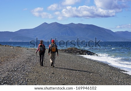 couple trekking on a beach in Patagonia along the straits of Magellan - stock photo