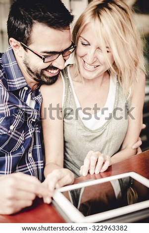 Couple using a digital tablet at the bar. - stock photo