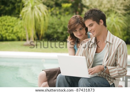 Couple using a laptop at home by swimming pool, exterior. - stock photo