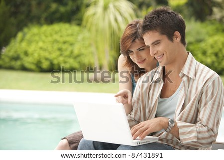 Couple using a laptop by swimming pool, hotel exterior.