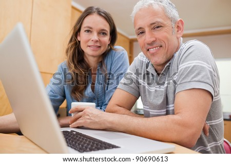 Couple using a laptop while having tea in their kitchen