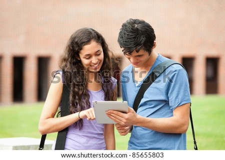 Couple using a tablet computer outside a building - stock photo