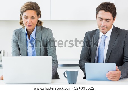 Couple using different media devices in kitchen before work - stock photo