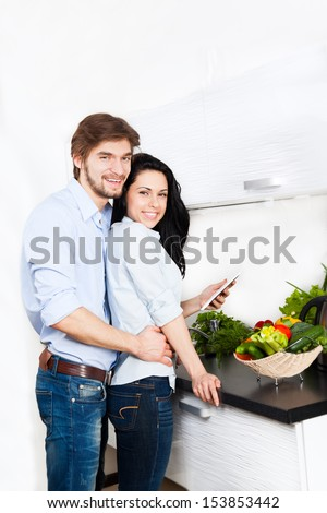 couple using electronic tablet at their kitchen home happy smile cooking, young family man and woman looking for recipe - stock photo