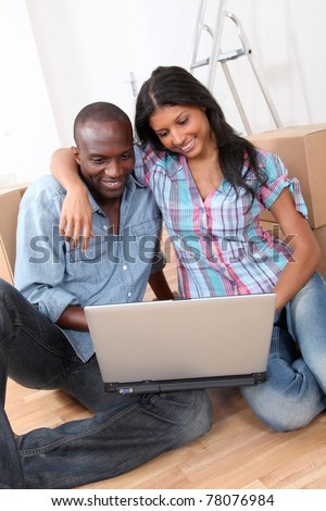 Couple using laptop computer in their new house
