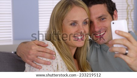 Couple using smartphone to webcam with family - stock photo