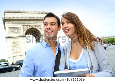 Couple using tablet by the Arch of Triumph - stock photo