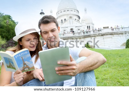 Couple using tablet in front of Sacre Coeur Basilica - stock photo