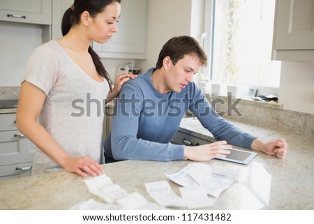 Couple using tablet pc to calculate finances in kitchen - stock photo