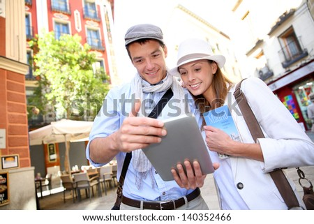 Couple visiting Madrid with help of digital tablet - stock photo
