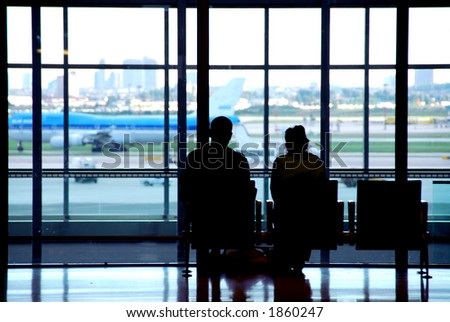 Couple waiting at the international airport terminal - stock photo