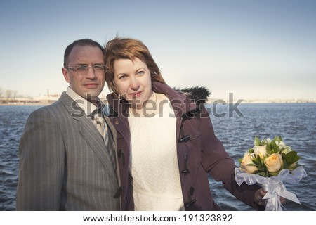 couple walk along the embankment of the river