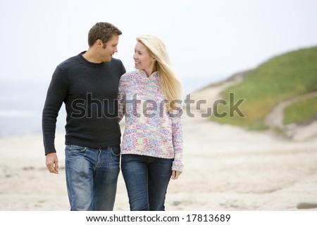 Couple walking at beach smiling - stock photo