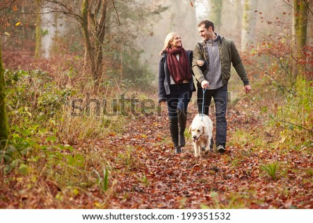 Couple Walking Dog Through Winter Woodland - stock photo