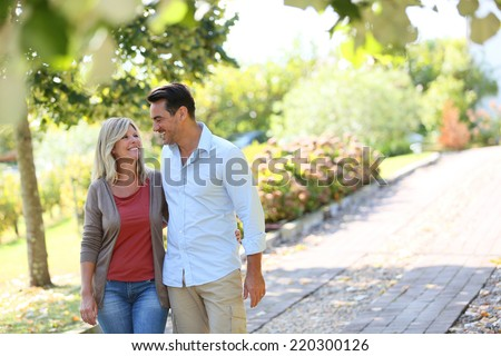 Couple walking hand in hand in park - stock photo