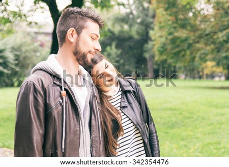 Couple walking happy in the park. Autumn and warm clothes. Relaxing during the weekend and enjoying the nature - stock photo